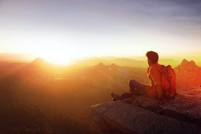 Photo: man sitting on the edge of a cliff overlooking scenery at sunset