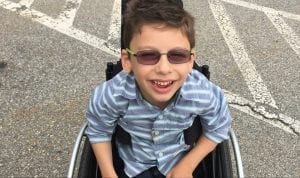 Photo: young boy with brown hair and sunglasses sitting in a parking lot, smiling