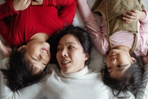 mom lying on bed with two children